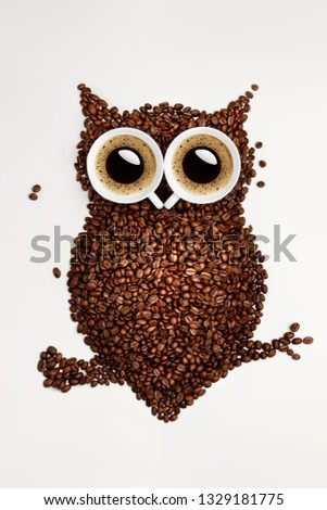 A funny owl made of roasted coffee beans and two cups. Creative concept photo of owl made of roasted coffee beans and two cups with refreshment espresso caffeine drink beverage on white background. #1329181775
