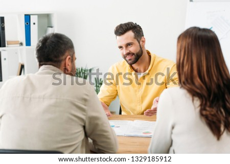 selective focus of advisor sitting at table and smiling to investors in office #1329185912