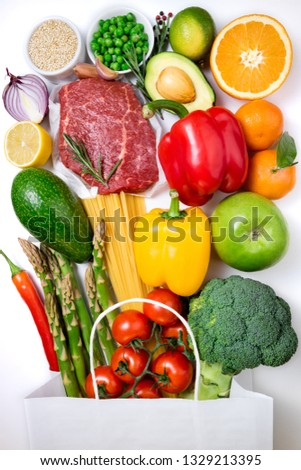 Healthy food background. Healthy food in paper bag meat, fruits, vegetables and pasta on white background. Shopping food in supermarket concept #1329213395
