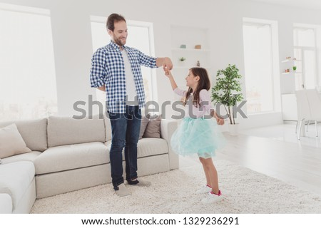Full length body size view of nice adorable attractive cheerful talented elegant pre-teen girl learning practicing training moves with daddy coach trainer assistant in modern light white interior room #1329236291