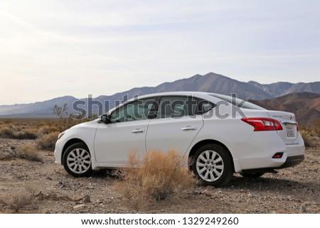 California, USA - Jan 21, 2019: White car Nissan Sentra in desert, California, US #1329249260
