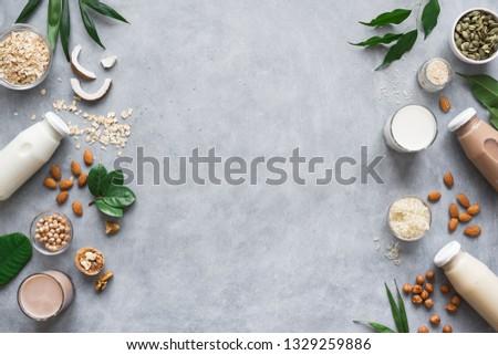 Various vegan plant based milk and ingredients on grey, top view, copy space. Dairy free milk substitute drink, healthy eating. Royalty-Free Stock Photo #1329259886