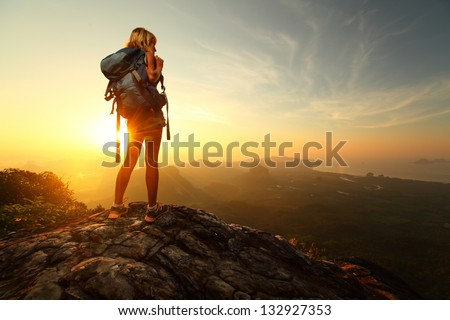 Hiker with backpack relaxing on top of a mountain and enjoying sunrise #132927353