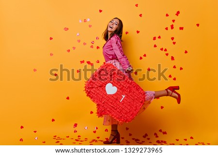 Glad girl in high heel shoes enjoying social networks. Fashionable european woman in pink attire laughing and dancing on yellow background. #1329273965