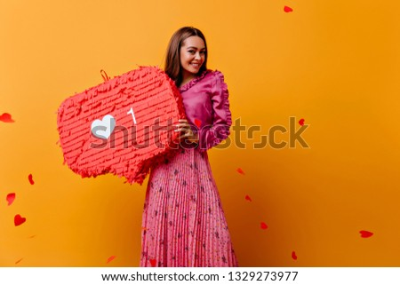 Gorgeous, joyful, cheerful girl posing with red decorations in her hands. Portrait of brown-haired woman in pink outfit against background of confetti in shape of hearts #1329273977