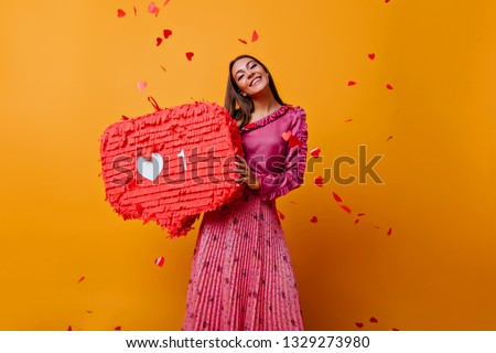Satisfied woman in pink outfit laughing in studio. Adorable caucasian girl in long skirt standing on yellow background. #1329273980