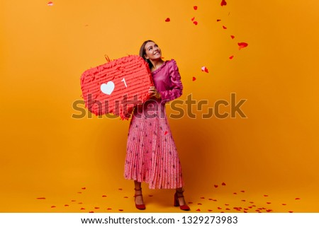 Dreamy romantic girl in great mood during photo shoot with big like in her hands. Studio female photo of model in fashionable blouse with frill #1329273983