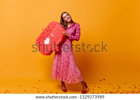 In room with orange cardboard background is stylish brown-haired woman in long skirt, holding big sign from instagram. Photo taken in orange and pink colors in studio #1329273989