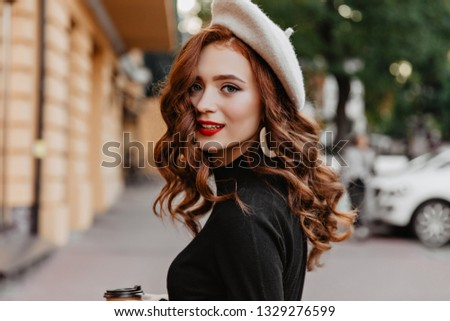 Gorgeous white girl with long wavy hair chilling in autumn day. Outdoor portrait of interested ginger female model with cup of coffee.