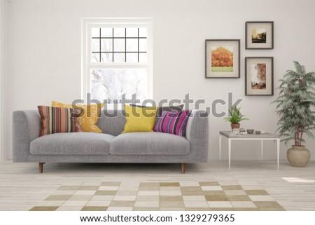 White stylish minimalist room with sofa and winter landscape in window. Scandinavian interior design. 3D illustration #1329279365