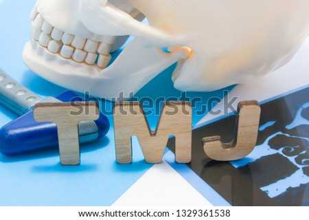 TMJ medical abbreviation of temporomandibular joint. TMJ letters surrounded by human skull with lower jaw, neurological hammer and radiographs. Concept of anatomy, pathology of temporomandibular joint #1329361538