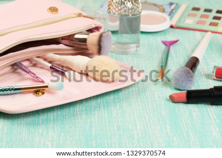 Pink makeup bag with brashes and decorative cosmetics on female desk. Turquoise wooden background #1329370574