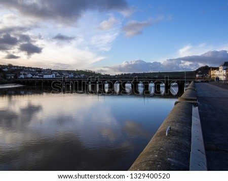 sunrise clouds reflecting in the River Torridge at Bideford`s ancient long bridge in Devon Royalty-Free Stock Photo #1329400520