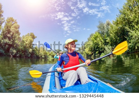 Happy family kayaking on the river. Active girl with her mother having fun enjoying adventurous experience with kayak on a sunny day during summer vacation #1329445448