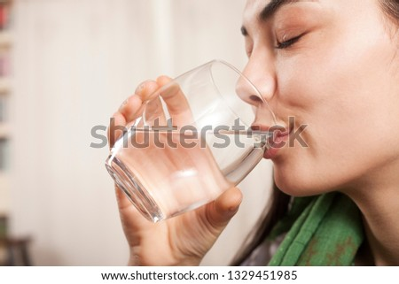 woman drinking a glass of water #1329451985