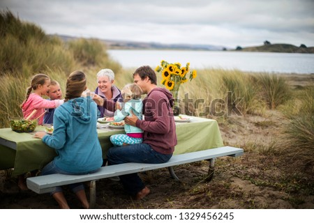 Happy multi-generational family enjoy an outdoor lunch at the beach. Royalty-Free Stock Photo #1329456245