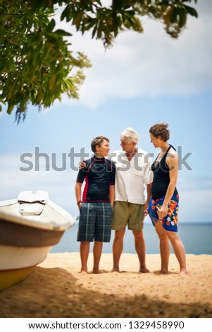 Boy standing next to dinghy at the beach with his parents. #1329458990