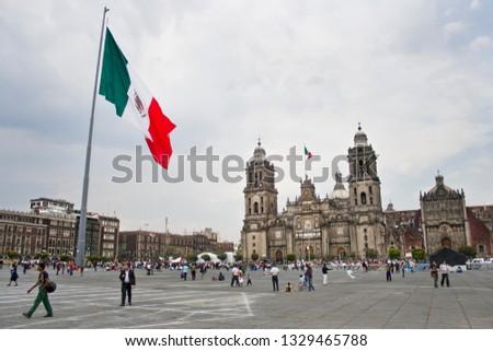 Mexico City, Mexico - March 23, 2012:  Mexico City Metropolitan Cathedral and Mexican flag at Zócalo in Mexcio City, Mexico #1329465788