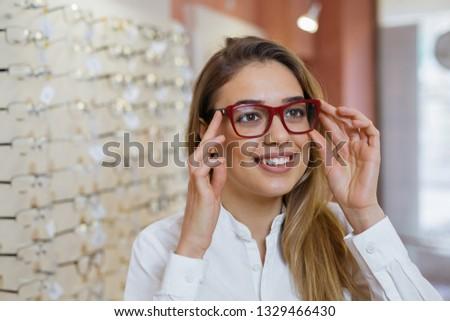 woman choosing eyeglasses in optic store #1329466430