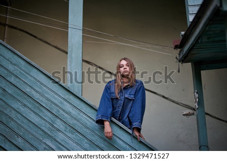 a girl stands on the stairs of an old house in a jean jacket #1329471527