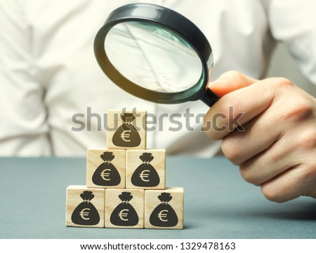Businessman holds magnifying glass over cubes with euro. Analysis of profits and revenues in the company. Distribution of money. The accumulation of capital. Budget planning. Business concept #1329478163