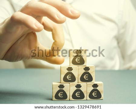 Businessman removes the cube with the image of the euro. Capital outflow. Pressure on small businesses. Bankruptcy. Economic recession. The concept of financial crisis. Sabotage of the economy. #1329478691