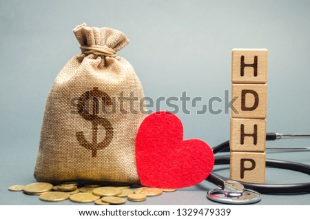 Wooden blocks with the word HDHP and money bag with dollar sign. High-deductible health plan concept. Health insurance plan with lower premiums and higher deductibles than a traditional health plan #1329479339