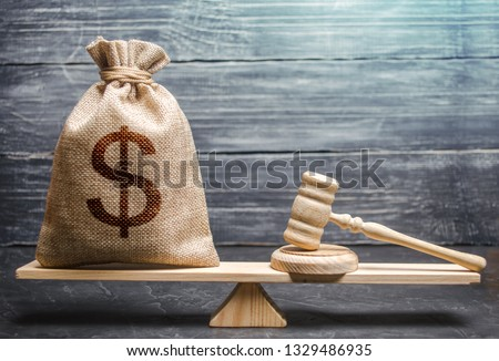 Bag of money with a dollar sign and a judge's hammer on the scales. Concept lobbying for the adoption of a law or a norms, corruption. Payment of fines and penalties. award of compensation for damage #1329486935