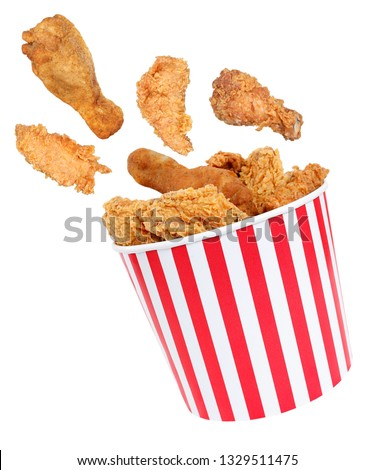Fried chicken nuggets flying around in red white striped box #1329511475