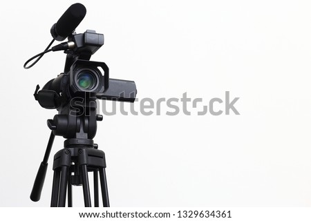 The video camera with the tripod isolated on white background. #1329634361