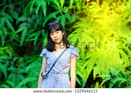 Woman with fern bush in background #1329646115