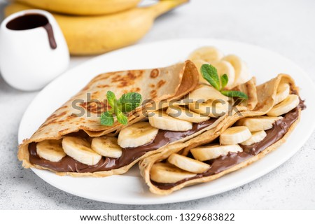 Crepes stuffed with chocolate spread and banana on white plate. Thin pancakes, blini. Sweet dessert. #1329683822