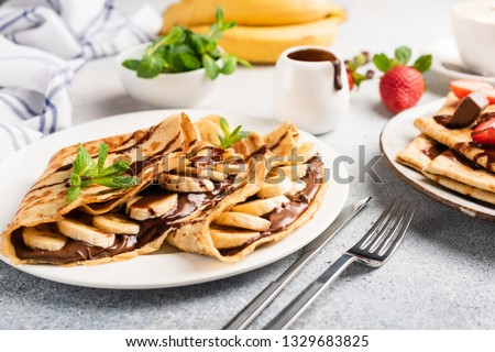Chocolate hazelnut spread and banana filled crepes on plate. Tasty crepes or blini with sweet sauce and fruits. Closeup view Royalty-Free Stock Photo #1329683825