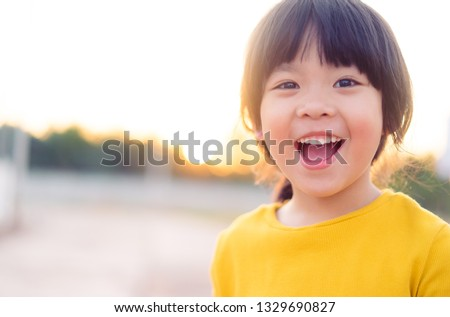 Happy Little asian girl child showing front teeth with big smile and laughing: Healthy happy funny smiling face young adorable lovely female kid.Joyful portrait of asian elementary school student.  #1329690827