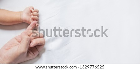 Asian parent hands holding newborn baby fingers, Closeup mother's hand holding their new born baby. Together love harmony peace family nursery healthcare and medical father's day concept banner #1329776525