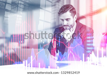 Serious young businessman working with laptop at office table over skyscraper background with double exposure of forex graphs. Stock market concept. Toned image #1329852419