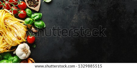 Italian food background. Healthy food background with pasta, tomatoes, basil and spices on dark background. Horizontal with copy space.  #1329885515