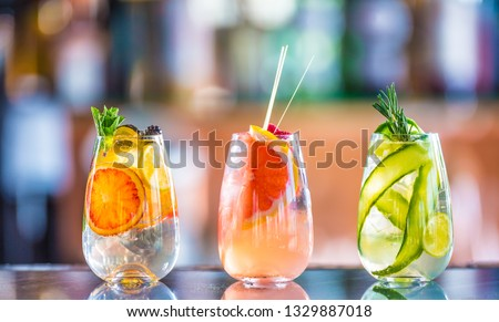 Tree colorful gin tonic cocktails in glasses on bar counter in pup or restaurant.  #1329887018
