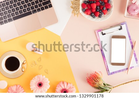 Female workspace with computer, summer yellow flowers bouquet on colorful pastel background. Flat lay of women's office desk. Top view feminine summer bright background.