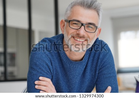 Portrait of smiling man with grey hair and glasses #1329974300