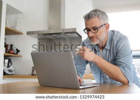 Man with computer at home in modern kitchen #1329974423
