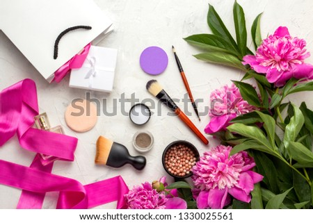 Gift white bag and packed with gift, blush, sponzhiki, brush, eye shadow, perfume bottle, pink ribbon and pink peonies on a light background. Top View. #1330025561