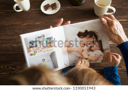 Hand senior woman and child holding a family photo album against the background of the a wooden table.