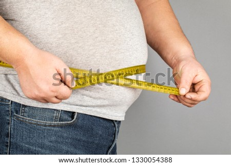 A man measures his fat belly with a measuring tape. on a gray background #1330054388