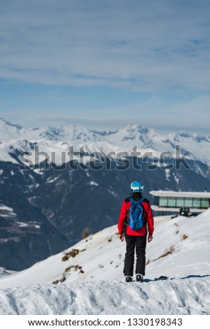 An anonymous tourist in a hat and sports wear admiring the gorgeous mountain winter landscape #1330198343
