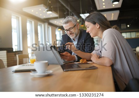 Young woman showing salesman stats on cellphone during informal meeting #1330231274