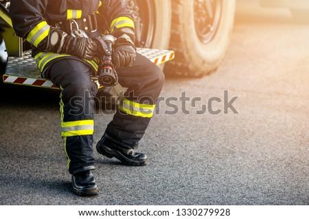 Firefighter Rescue man. Firefighter in uniform and  helmet near fire engine.