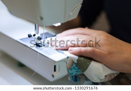 Seamstress hands at work, threads and needles #1330291676