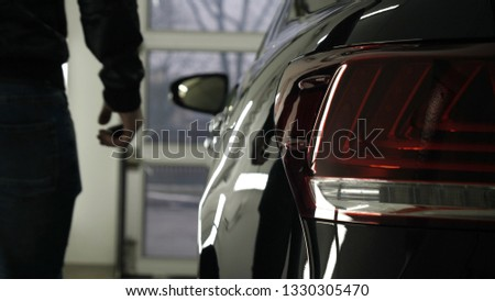 A man in the garage (car service) Checks the car alarm and then goes off (comes in) turning off (turning on) the lights behind him. Concept of: Auto garage, Security.  #1330305470