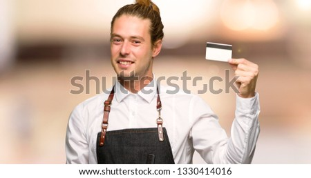 Barber man in an apron holding a credit card in a barber shop